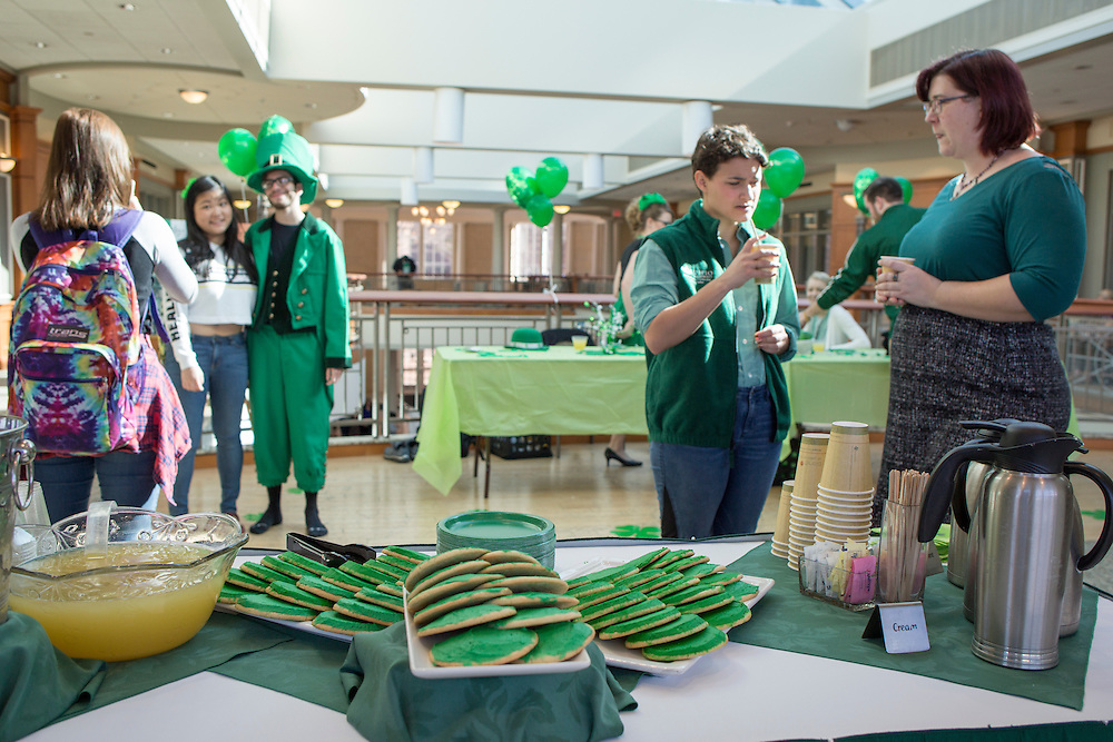 Claire Seid, a junior Multicultural Leadership Ambassador studying sociology, and Sarah Jenkins, far right, the program coordinator for the Women's Center, enjoy refreshments while Francisco Cintron, a sophomore studying history gets his picture taken dressed as a leprechaun at the St. Patrick's Day celebration hosted by the Office of Diversity and Inclusion on March 17, 2016.