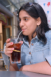 Portrait of teenage girl drinking coca cola outdoors in street café,