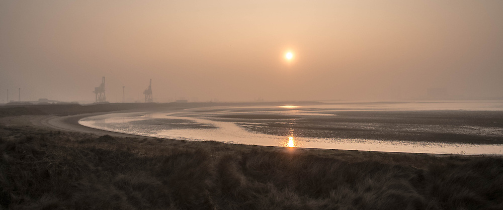 © Licensed to London News Pictures. <br /> 18/03/2015. <br /> <br /> Redcar, Teesside.<br /> <br /> The sun sets over the River Tees as fog and mist descends in an area known as South Gare near Redcar on Teesside.<br /> <br /> Photo credit : Ian Forsyth/LNP