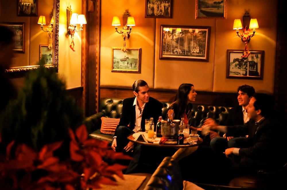 University students drink whiskey during a party at El Pingüino bar at the Caracas Country Club.