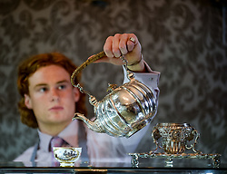 Bonham's staff member Harry Devlin with a rare silver tea kettle dated 1733 which is coming under the hammer in Edinburgh 14 June.<br /> <br /> &copy; Dave Johnston/ EEm