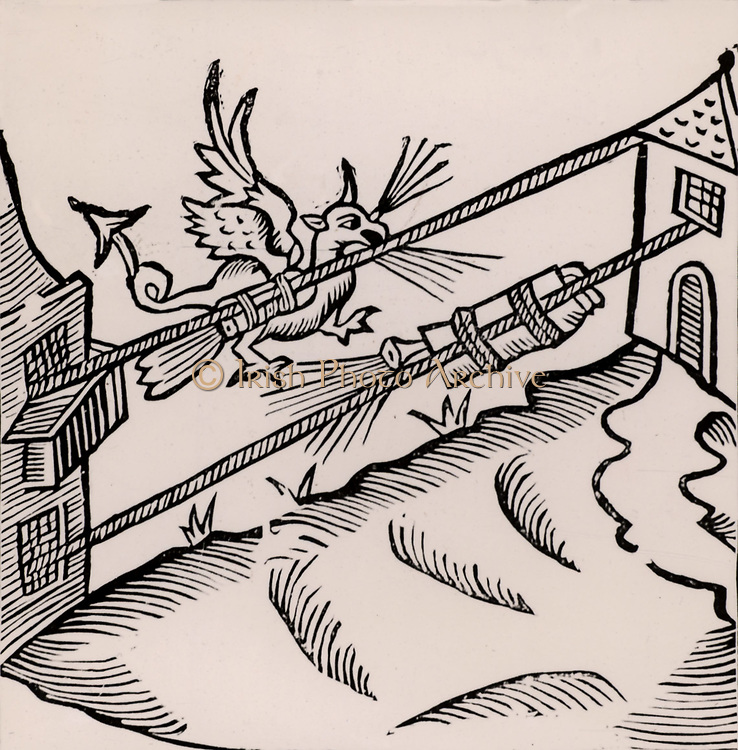 A Firework display: The figure of a dragon breathing fire is attached to a rocket tied to a rope stretched between two buildings.   Woodcut from 'Recreations mathematiques' by Jean Leurechon (Rouen, 1628).