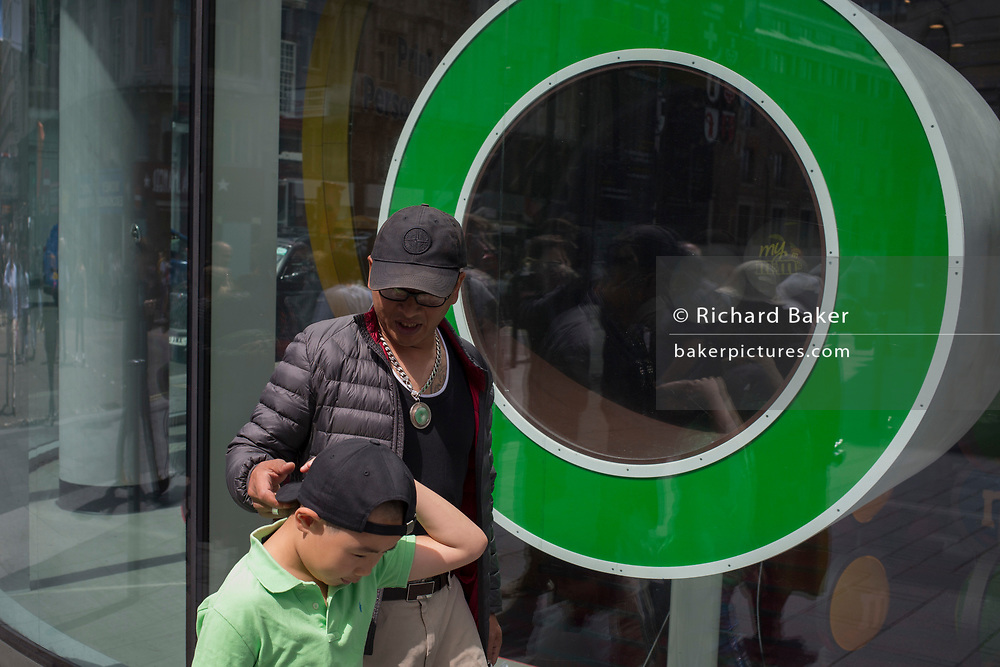 A man and young boy walk past one of the green cirlces outside M&M's World's Leicester Square store, on 31st July 2017, in London, England.