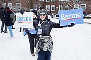 Brooklyn, NY - 2 March 2019. A woman coming in to Bernie Sanders' first rally for the 2020 presidential primary at Brooklyn College carries 2 Bernie signs.