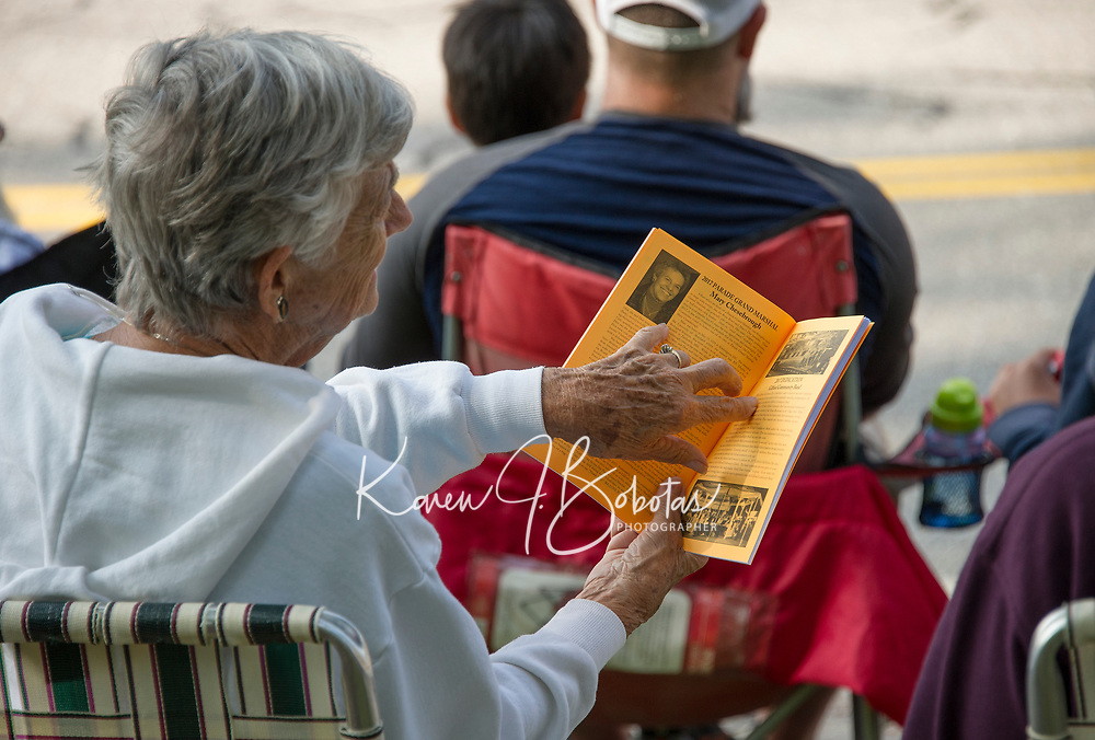 A woman sits reading about Grand Marshall Mary Chesebrough in the program while she waits for the 98th annual Gilford Old Home Day parade to begin.   (Karen Bobotas/for the Laconia Daily Sun)