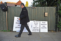 TWICKENHAM LONDON. A protester sets up banners against a garden fence. The Richmond Coalition Against the State Visit greet Pope Benedict XVI as he visits St Mary's University in Twickenham for a Celebration of Roman Catholic education. The Coalition oppose the Pope's opinions on condom use, abortion, gay rights and education. 17 September 2010. STEPHEN SIMPSON.