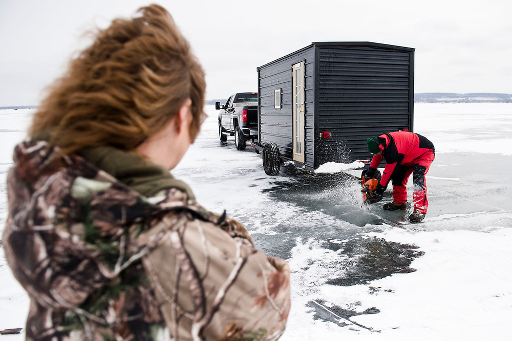 "PIPE, WI -FEB. 16, 2015: Joe Wettstein, 59, drills through the ice with a chainsaw to help make his 16th spear fishing hole of the season for various friends and family Monday, Feb. 16, 2015 on Lake Winnebago. He is watched by Connie Petska, 46, who will be fishing in the hole with Darin Callahan, 44. ""It's a waiting game,"" she says. ""You sit and wait."" 13,000 licenses were sold for the 2015 sturgeon spearing season, and 233 fish were caught Monday between all of the registration stations, with 62 being registered in Stockbridge. The season started Feb. 14, 2015 and lasted until Feb. 21, 2015 on Lake Winnebago with a total of 1870 sturgeon speared. The average success rate for spearers is 10-12% and some people go years without spotting anything from their shanty. Lauren Justice for The New York Times"