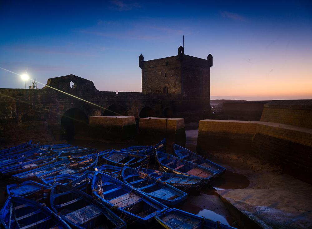 ESSAOUIRA, MOROCCO - CIRCA MAY 2018:  Sunset over the port of Essaouria and the famous Castelo Real of Mogador.