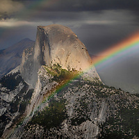 Rainbow and spot of light over Half Dome during a summer thunderstorm, Yosemite National Park, California.