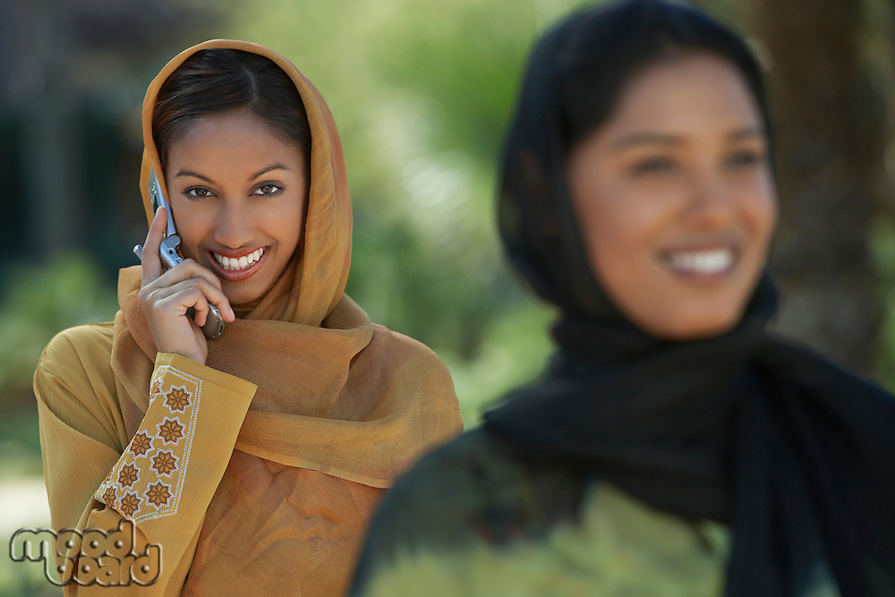 Two muslim woman, smiling, one talking on mobile, selective focus