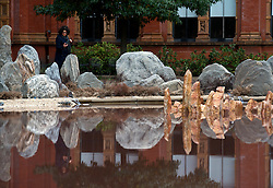 © Licensed to London News Pictures.31/10/2013. London, UK. A visitor looks at the installation of the Chinese artist Xu Bing by the lake of he John Madejski Garden at V&A Museum, where his new installation is shown. Travelling to the Wonderland inspired by the classic Chinese fable Tao Hua Yuan (The Peach Blossom Spring). The V&A invited Xu Bing to create a major new work to coincide with the Museum's forthcoming exhibition, Masterpieces of Chinese Painting 700 – 1900.Photo credit : Peter Kollanyi/LNP