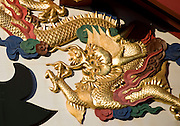 Photo shows a detail of the colorfully decorative exterior of the main Seiden hall inside the grounds of Shuri-jo Castle in Naha, Okinawa Prefecture, Japan, on June 24, 2012. The Seiden functioned as the central structure of the Ryukyu kingdom for over 500 years and is decorated with a wide variety of carvings - this one of a golden dragon. Photographer: Robert Gilhooly