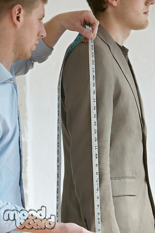 Tailor measuring jacket sleeve on man side view close up