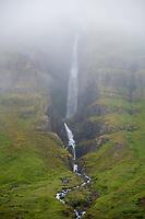 A waterfall in the fog. Mjóifjörður, East fiords of Iceland.