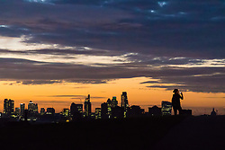 Primrose Hill, London, September 27th 2016. A woman photographs the pre-dawn skyline on Primrose Hill as a new day breaks over London. &copy;Paul Davey<br /> FOR LICENCING CONTACT: Paul Davey +44 (0) 7966 016 296 paul@pauldaveycreative.co.uk