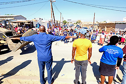 JOHANNESBURG, SOUTH AFRICA - MAY 08: Volunteers and food distribution officials instruct people to social distance outside a food distribution centre in Diepsloot on May 08, 2020 in Diepsloot, South Africa. In partnership with with government and Celebration Church, Engen Fuel Retailers contributed food parcels for over 4000 familes in Diepsloot during lockdown level 4. (Photo by Dino Lloyd)
