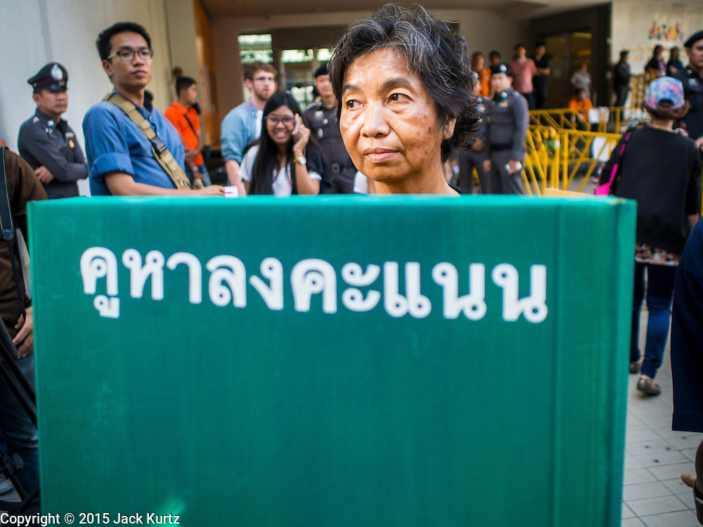 "14 FEBRUARY 2015 - BANGKOK, THAILAND:  A pro-democracy protestor stands behind a mock ballot box in Bangkok. Dozens of people gathered in front of the Bangkok Art and Culture Centre in Bangkok Saturday to hand out red roses and copies of George Orwell's ""1984."" Protestors said they didn't support either Red Shirts or Yellow Shirts but wanted a return of democracy in Thailand. The protest was the largest protest since June 2014, against the military government of General Prayuth Chan-Ocha, who staged the coup against the elected government. Police made several arrests Saturday afternoon but the protest was not violent.     PHOTO BY JACK KURTZ"