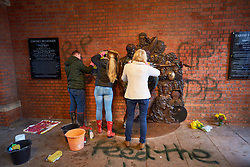 © Licensed to London News Pictures. 27/03/2018. AYLESBURY, UK.  The new David Bowie statue has been vandalised less than 48 hours after it was unveiled. Black spray paint has been used to deface the statue itself and write 'RIP DB' and 'Feed The Homeless First' despite no public money being involved. In this picture: Sue Stopps (white coat), wife of music promoter David Stopps (not pictured) who organised the crowdfunding campaign, attempts to clean the statue. Photo credit: Cliff Hide/LNP