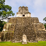 Temple 2, also known as the Temple of the Masks, in the Tikal Maya ruins in northern Guatemala, now enclosed in the Tikal National Park. At the bottom in front is a stela that once held commemorative inscriptions that have since worn away.