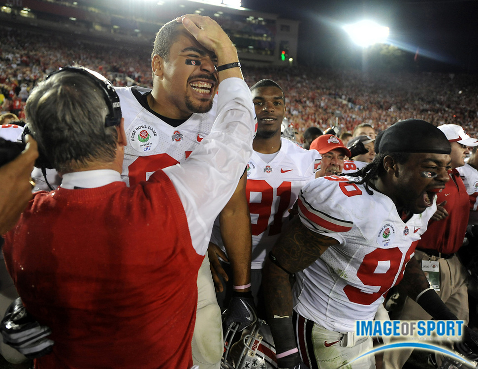 Jan 1, 2010; Pasadena, CA, USA; Ohio State Buckeyes coach Jim Tressel (left) congratulates defensive linemen Lawrence Wilson (87), center, and Thaddeus Gibson (90) after the 2010 Rose Bowl aganst the Oregon Ducks at the Rose Bowl. Ohio State defeated Oregon 26-17.