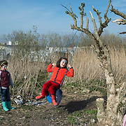 Calais, France. The refugee camp known as the 'Jungle'. Kurdish Iraqi refugee children play on a swing.