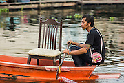 04 JANUARY 2012 - BANGKOK, THAILAND:  A man paddles his boat on Khlong Phra Khanong near Wat Mahabut. The temple was built in 1762 and predates the founding of the city of Bangkok. Just a few minutes from downtown Bangkok, the neighborhoods around Wat Mahabut are interlaced with canals and still resemble the Bangkok of 60 years ago. Wat Mahabut is a large temple off Sukhumvit Soi 77. The temple is the site of many shrines to Thai ghosts. Many fortune tellers also work on the temple's grounds.   PHOTO BY JACK KURTZ