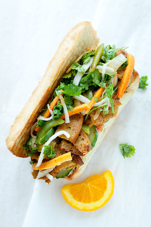 A vegan version of the Vietnamese sandwich called Banh Mi made with seitan, carrots and cilantro on a baguette.