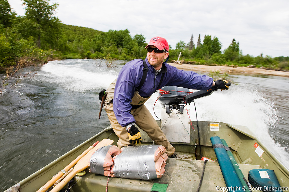 Sportfishing guide, Anders Gustafson, drives a jet drive powered skiff on the Koktuli River in Bristol Bay, Alaska.