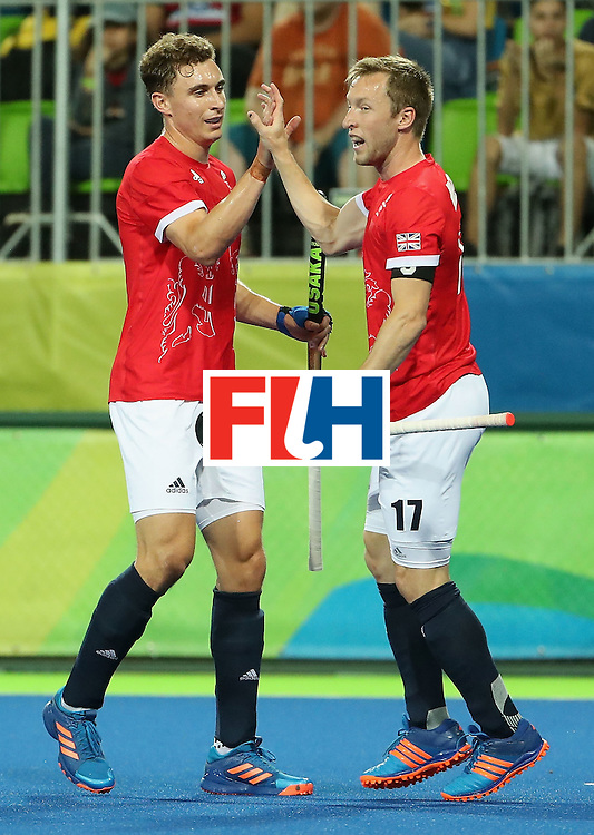 RIO DE JANEIRO, BRAZIL - AUGUST 09:  Barry Middleton #17 (R) of Great Britain high fives Harry Martin #9 after Middleton scored a goal against Brazil during the hockey game on Day 4 of the Rio 2016 Olympic Games at the Olympic Hockey Centre on August 9, 2016 in Rio de Janeiro, Brazil.  (Photo by Christian Petersen/Getty Images)