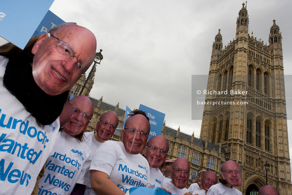 """Politcal action group Avaaz wear Rupert Murdoch masks outside Parliament during News International phone hacking scandals. Avaaz--meaning """"voice"""" in several European, Middle Eastern and Asian languages--launched in 2007 with a simple democratic mission: organize citizens of all nations to close the gap between the world we have and the world most people everywhere want."""
