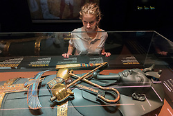 "© Licensed to London News Pictures. 01/11/2019. LONDON, UK. A staff member views gold decorations found on the mummy of Tutankhamun.  Preview of ""Tutankhamun, Treasures of the Golden Pharoah"" at the Saatchi Gallery in Chelsea.  The exhibition celebrates the 100th year anniversary of the opening of Tutankhamun's tomb and displays 150 works in the largest collection of Tutankhamun's treasures ever to leave Egypt.  The show runs 2 November to 3 May 2020.  Photo credit: Stephen Chung/LNP"