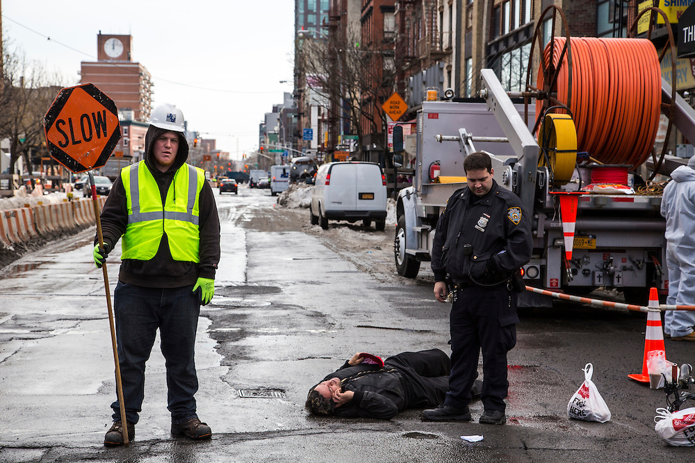 A man lies in the street talking on his phone after falling off his bike, an NYPD police officer stands next to him and workman holds a SLOW sign to control the traffic on East Houston Street in Lower East Side, New York City, New York, Unites States of America. <br /> (photo by Andrew Aitchison / In pictures via Getty Images)