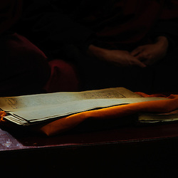 Monks praying early morning while a beam of sunrays lights up a holy scripture, Tibet.