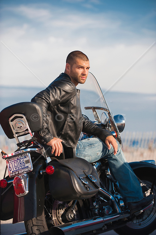 man with a shaved head on a motorcycle by the ocean