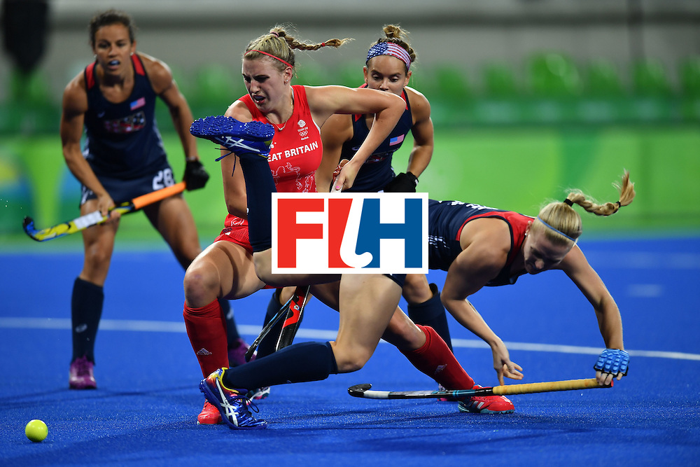 USA's Stefanie Fee (R) falls over Britain's Lily Owsley during the women's field hockey Britain vs the USA match of the Rio 2016 Olympics Games at the Olympic Hockey Centre in Rio de Janeiro on August, 13 2016. / AFP / MANAN VATSYAYANA        (Photo credit should read MANAN VATSYAYANA/AFP/Getty Images)