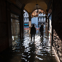 People walks in Central Venice during seasonal High Tide. A few days of exceptional high tides up to 120cm are expected during the next few days