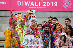 © Licensed to London News Pictures. 03/11/2019. London, UK. Dancers in colourful costumes takes a selfie during the Diwali celebrations in London's Trafalgar Square. Hundreds of Hindus, Sikhs, Jains and people from all communities attend Diwali celebrations in London's Trafalgar Square. Diwali s celebrated each year with a free concert of traditional, religious and contemporary Asian music and dance. Photo credit: Dinendra Haria/LNP
