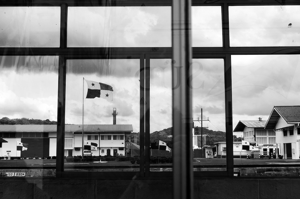 MIRAFLORES LOCKS - PANAMA CANAL<br /> Photography by Aaron Sosa<br /> Panama City, Panama 2012<br /> (Copyright &copy; Aaron Sosa)<br /> <br /> Flag of Panama located in the Miraflores Visitor Center, view from the work area of the Canal.<br /> <br /> The Panama Canal is an 77.1-kilometre (48 mi) ship canal in Panama that connects the Atlantic Ocean (via the Caribbean Sea) to the Pacific Ocean. The canal cuts across the Isthmus of Panama and is a key conduit for international maritime trade. There are locks at each end to lift ships up to Lake Gatun (26m (85ft) above sea-level) which was used to reduce the amount of work required for a sea-level connection. The current locks are 33.5m (110ft) wide although new larger ones are proposed.<br /> <br /> Work on the canal, which began in 1881, was completed in 1914, making it no longer necessary for ships to sail the lengthy Cape Horn route around the southernmost tip of South America (via the Drake Passage) or to navigate the dangerous waters of the Strait of Magellan. One of the largest and most difficult engineering projects ever undertaken, the Panama Canal shortcut made it possible for ships to travel between the Atlantic and Pacific Oceans in half the time previously required. The shorter, faster, safer route to the U.S. West Coast and to nations in and along the Pacific Ocean allowed those places to become more integrated with the world economy.