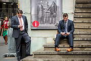 Two men in suits are taking a break to text and phone on the stairs of the old Stock Exchange as they are leaving the NYSE Euronext Stock Exchange on Wall Street.