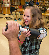 Gracie Henderson tries out her new prosthetic arm created with a 3D printer by engineering students at Washington High School, November 2, 2015.