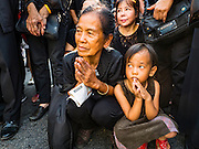 16 DECEMBER 2015 - BANGKOK, THAILAND: A woman and her daughter pray during the funeral procession for Somdet Phra Nyanasamvara, who headed Thailand's order of Buddhist monks for more than two decades and was known as the Supreme Patriarch. He was ordained as a Buddhist monk in 1933 and appointed as the Supreme Patriarch in 1989. He was the spiritual advisor to Bhumibol Adulyadej, the King of Thailand when the King served as a monk in 1956. Tens of thousands of people lined the streets during the procession to pray for the Patriarch.     PHOTO BY JACK KURTZ