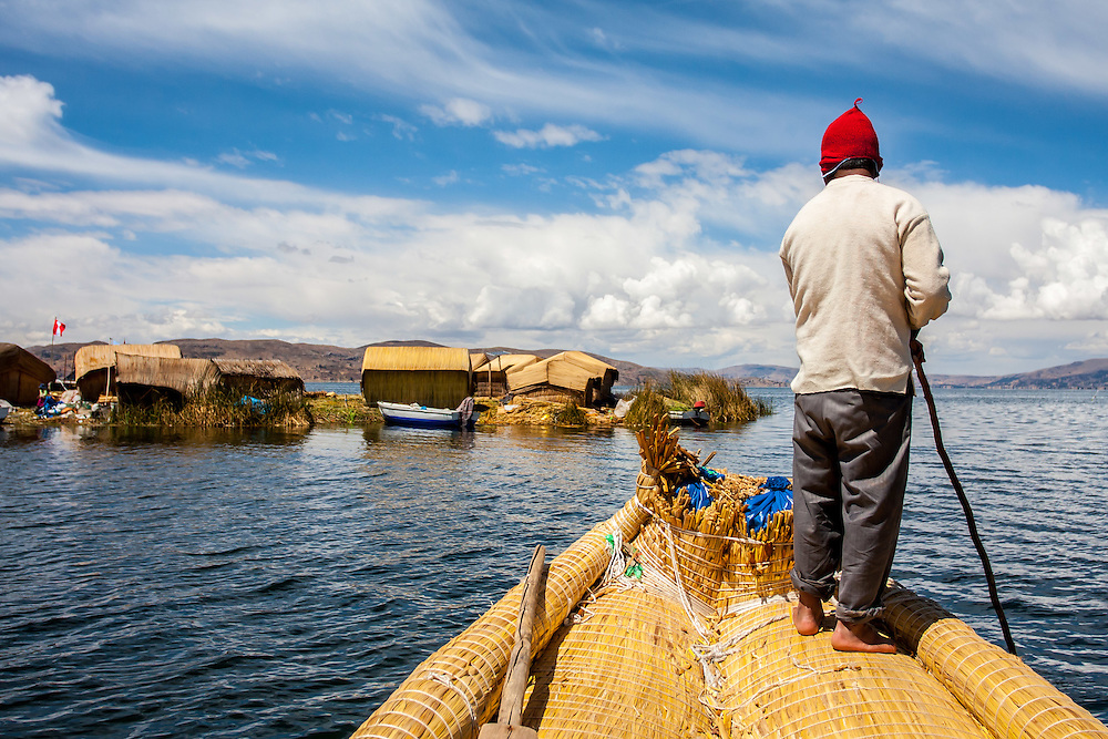 man rowing traditional reed boat, floating islands (Islas Flotantes), Uros islands, Lake Titicaca, Puno area, Peru, South America