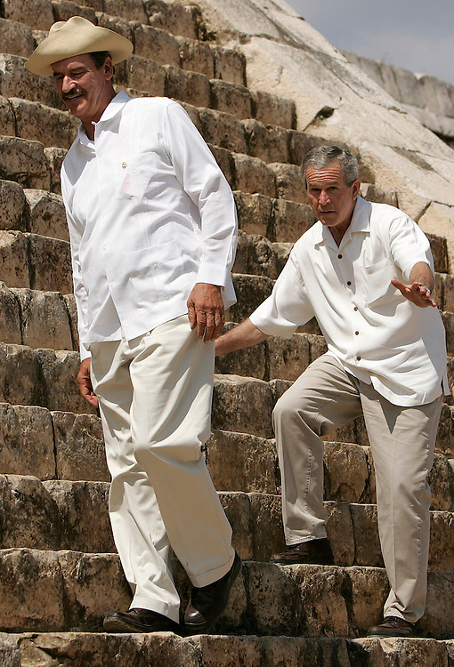U.S. President George W. Bush (C) pretends to loose his balance as he and Mexico's President Vicente Fox (L) and Canadian Prime Minister Stephen Harper walk the steps of an ancient Mayan Pyramid during a tour of the archaeological Ruins in Chichen-Itza, Mexico on Thursday 30 March 2006. Bush is in Mexico for a three way North American summit with and today and tomorrow. Border security and immigration issues are expected to dominate the talks.