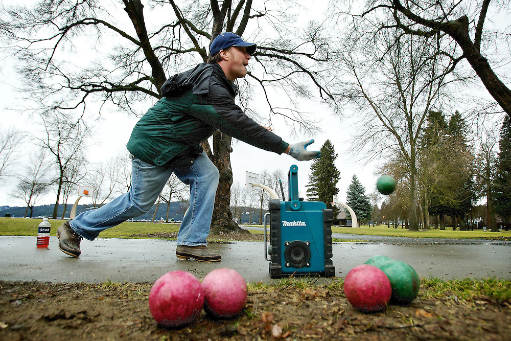 Don Enlow tosses a ball down the pathway during a game of open bocce ball Thursday in City Park. Enlow and his friend Mick Arzola typically play frisbee golf, but the weather conditions were more favorable to a roaming game of bocce ball.