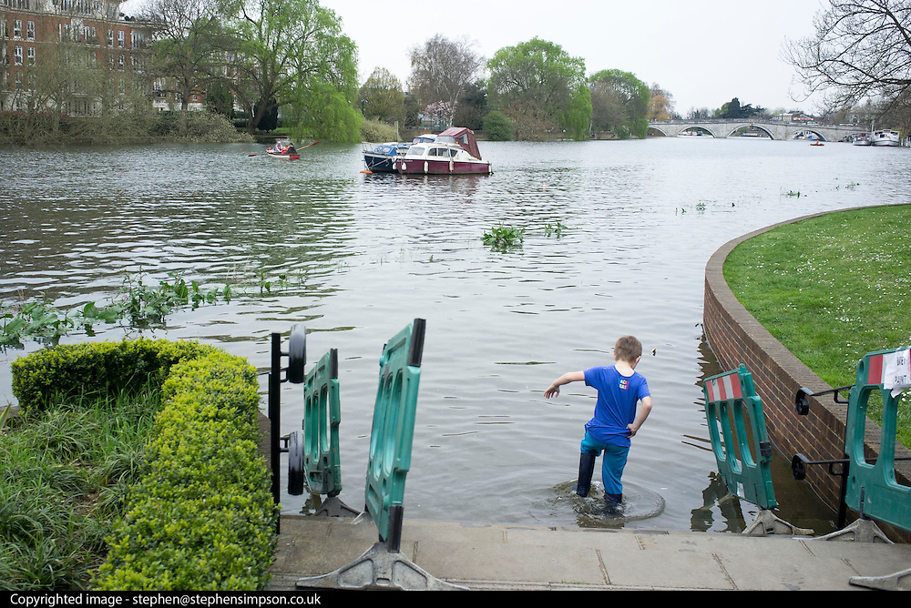 © Licensed to London News Pictures. 30/03/2014. Richmond, UK. A young boy braves the flooded path in a pair of wellies The high tide on the River Thames causing flooding in Richmond this afternoon 30th March 2014. Photo credit : Stephen Simpson/LNP