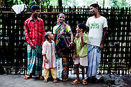 (L-R) Mohd. Shahin Alom (13, son), Mahfuza Akhter (5, daughter), Shahida Begum (35), Shakil Alom (7, son), Mohd. Abu Taleb (41, husband). .Shahida Begum, 35, poses for a family portrait in her home in Palashbari Villlage, Taragonj, Rangpur, Bangladesh on 18th September 2011. She contributes to the family income by working as a saleswoman, earning 3500 - 5000 Bangladeshi Taka per month. She is one of many rural Bangladeshi women trained by NGO CARE Bangladesh as part of their project on empowering women in this traditionally patriarchal society. Named 'Aparajitas', which means 'women who never accept defeat', these women are trained to sell products in their villages and others around them from door-to-door, bringing global products from brands such as BATA, Unilever and GDFL to the most remote of villages, and bringing social and financial empowerment to themselves.  Photo by Suzanne Lee for The Guardian
