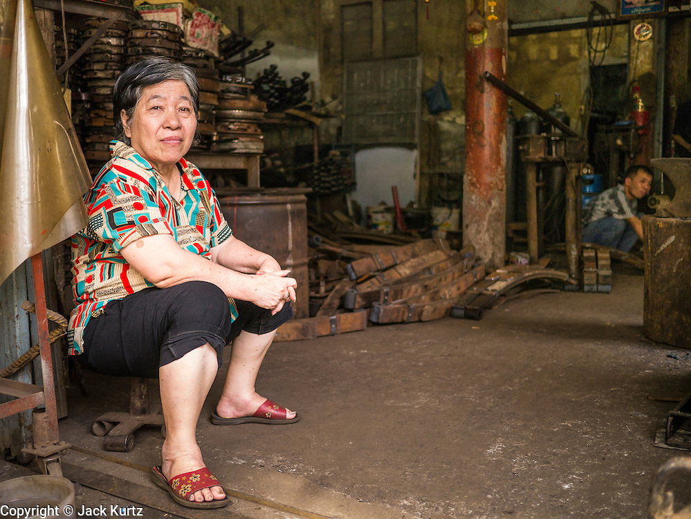 20 APRIL 2013 - BANGKOK, THAILAND:  A woman sits in the doorway of her mechanical shop in Talat Noi (Talat means Market, Noi means Small. Literally Small Market). The Talat Noi neighborhood in Bangkok started as a blacksmith's quarter. As cars and buses replaced horse and buggy, the blacksmiths became mechanics and now the area is lined with car mechanics' shops. It is one the last neighborhoods in Bangkok that still has some original shophouses and pre World War II architecture. It is also home to a  Teo Chew Chinese emigrant community.   PHOTO BY JACK KURTZ