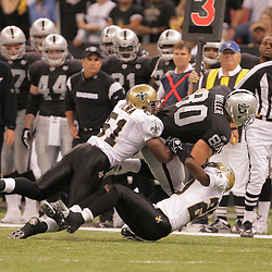 2008 October, 12: Oakland Raiders tight end Zach Miller (80) is tackled by Saints defenders Jonathan Vilma (51) and Randall Gay (20) during a week six regular season game between the Oakland Raiders and the New Orleans Saints at the Louisiana Superdome in New Orleans, LA.