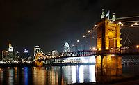 The Roebling Suspension Bridge at night along the Cincinnati Skyline
