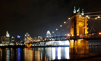 The Roebling Suspension Bridge at night along the Cincinnati Skyline